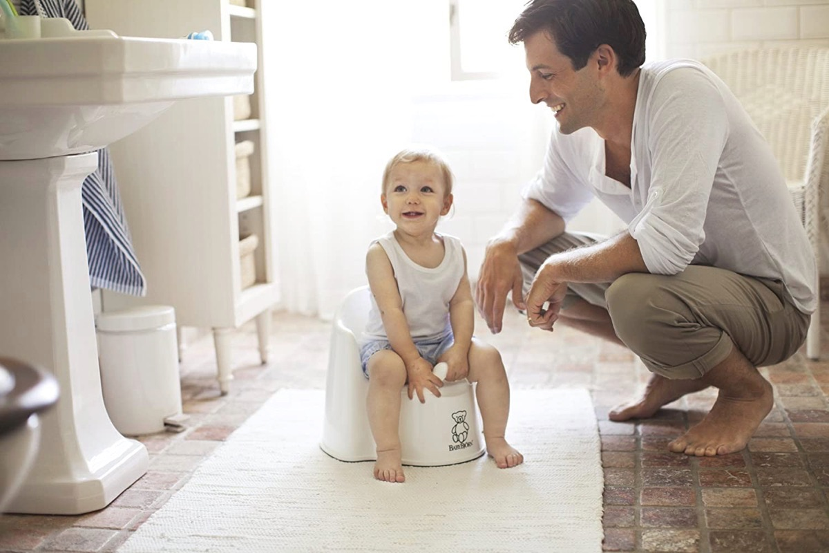 Toddler sitting on a potty seat with a dad crouching next to him.